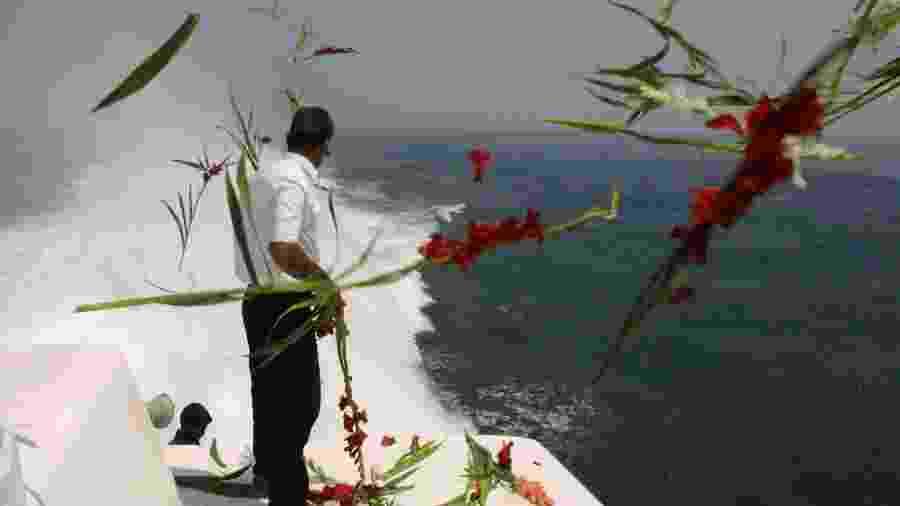 3.jul.01 - Parente de vítima iraniana de queda de avião derrubado pelos EUA em 1988 joga flores nas águas do Golfo Pérsico, local da tragédia  - Behrouz Mehri - 3.jul.01/AFP)