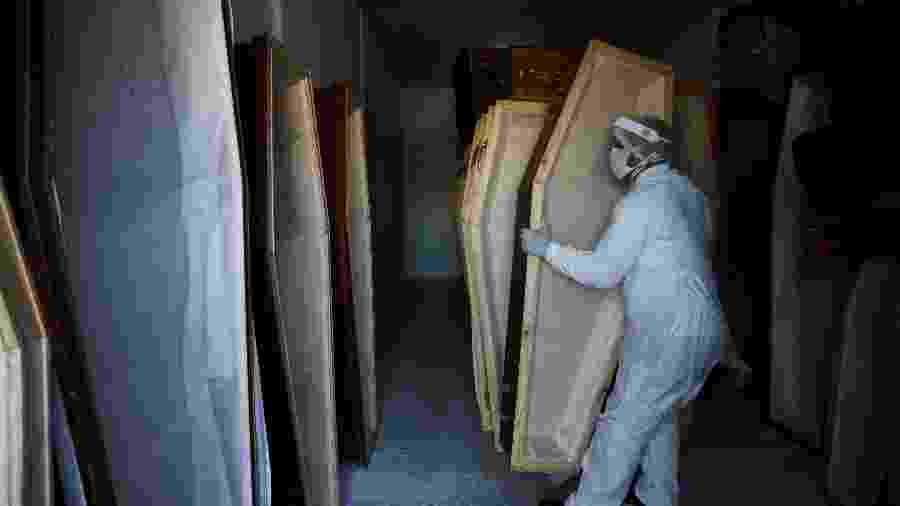 Trabalhador, vestindo roupas de proteção, prepara caixões em meio ao surto da covid-19 em Manaus - BRUNO KELLY/REUTERS