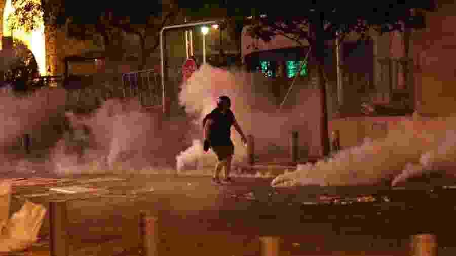 Um manifestante é retratado em meio à fumaça de gás lacrimogêneo durante protesto perto do parlamento em Beirute, Líbano - Reuters