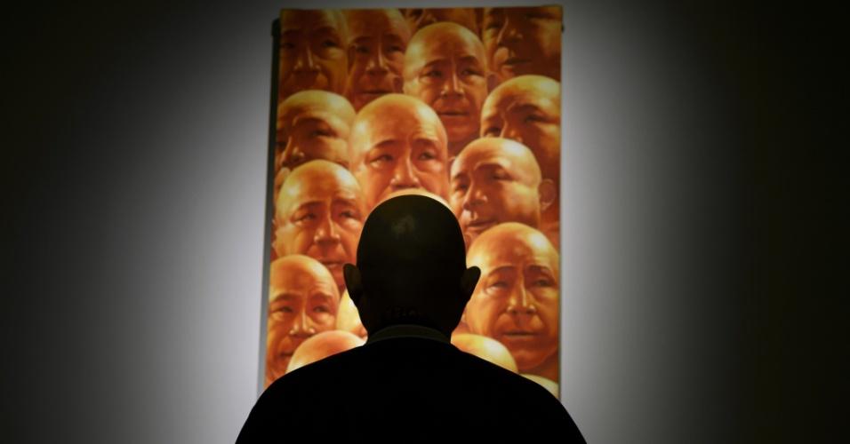 10.nov.2016 - Fang Lijun, artista contemporâneo, posa em frente a obra que representa a si mesmo, em exposição no Museu Ariana em Genebra