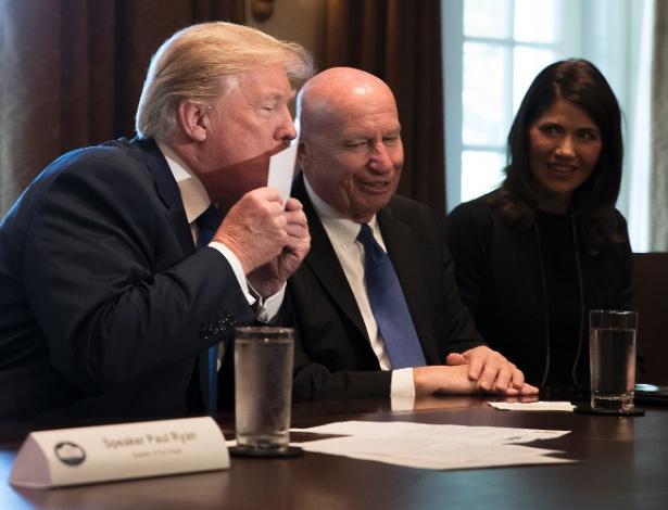 """Presidente dos EUA, Donald Trump, beija uma declaração de """"cartão postal"""", parte do esboço das propostas de impostos apenas divulgadas pelo Partido Republicano, na Casa Branca em Washington"""