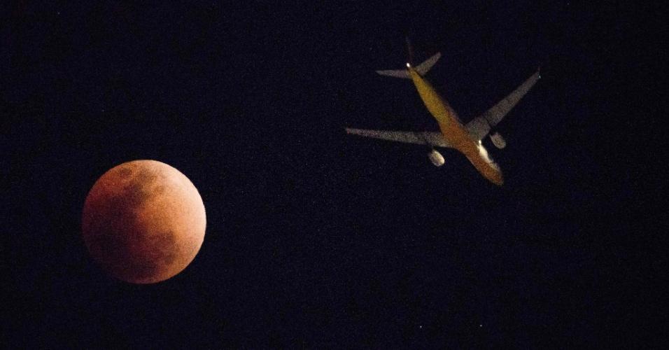 """31.jan.2018 - Avião passa próximo a uma """"superlua azul de sangue com eclipse"""" em Hong Kong, China"""