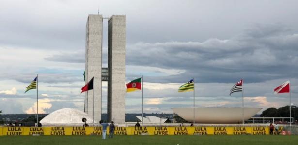 """Manifestantes pró-Lula colocam faixas com o escrito """"Lula livre"""" em grades em frente ao Congresso"""