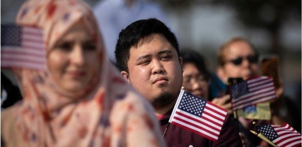 Novos cidadãos americanos agitam bandeiras do país durante cerimônia de naturalização - Getty Images