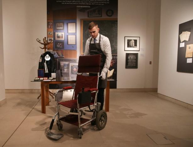 Assistente da galeria posa com a cadeira de rodas motorizada que pertenceu ao físico teórico britânico Stephen Hawking