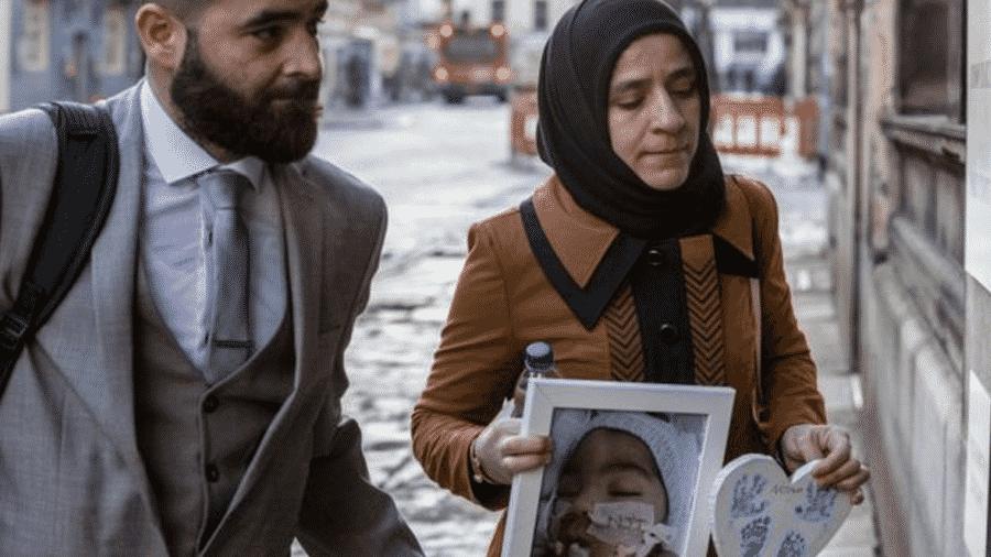 O pai e a mãe de Midrar Ali, com um retrato do bebê, entram no tribunal de Manchester para uma nova audiência do caso - Reprodução