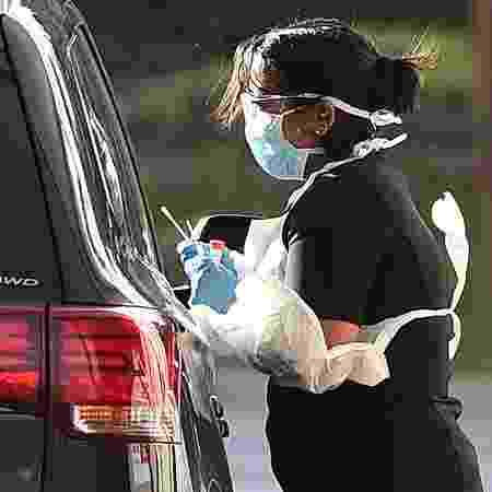 Integrante da equipe médica faz teste para coronavírus em um trabalhador na Grande Londres, em 28 de março  - GLYN KIRK/AFP