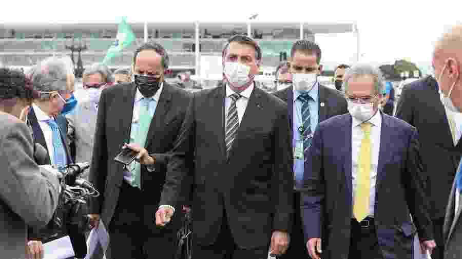 Presidente Jair Bolsonaro caminha ao lado de Braga Netto e Paulo Guedes - Marcos Correa/PR