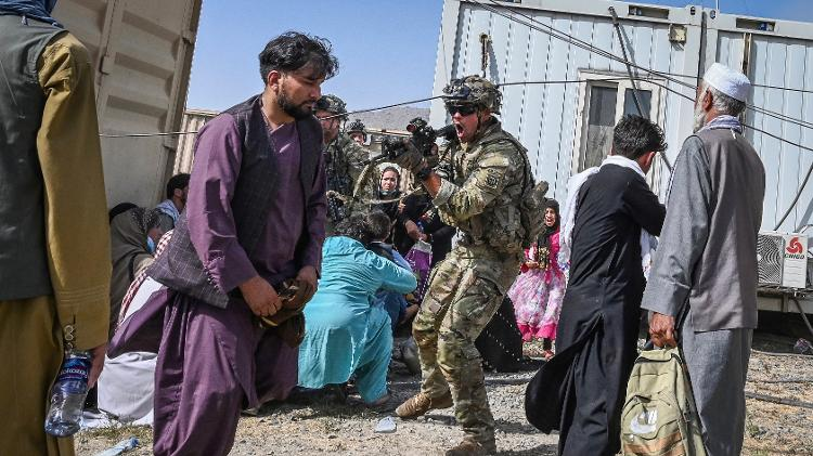 16.Aug.2021- American soldier points gun at an Afghan passenger at the airport in Kabul, Afghanistan - Wakil Kohsar/AFP - Wakil Kohsar/AFP