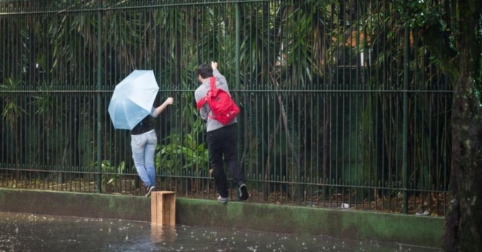 8.ago.2015 - Casal usa grades do estádio do Palmeiras para evitar a rua alagada