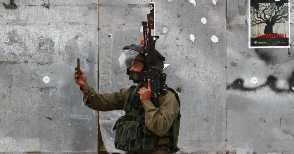 14.out.2015 - Membro das forças de segurança israelenses tira foto pelo celular enquanto carrega armamento na cidade de Belém, na Cisjordânia. A região volta a ser palco de confrontos violentos entre palestinos e israelenses, o que aumentam os temores de uma terceira intifada, o conhecido levante palestino