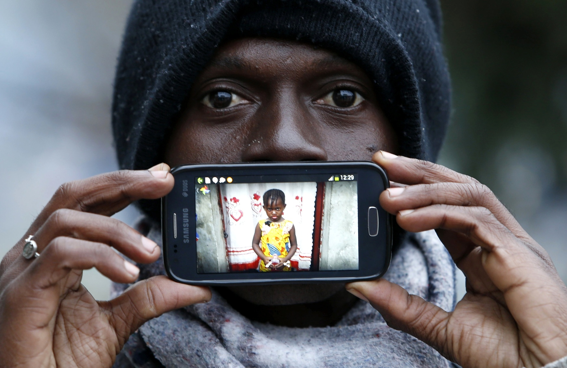 Papi, de Kinshasa, no Congo, mostra uma imagem de sua filha Gisele enquanto aguarda para cruzar a fronteira da Eslovênia com a Áustria