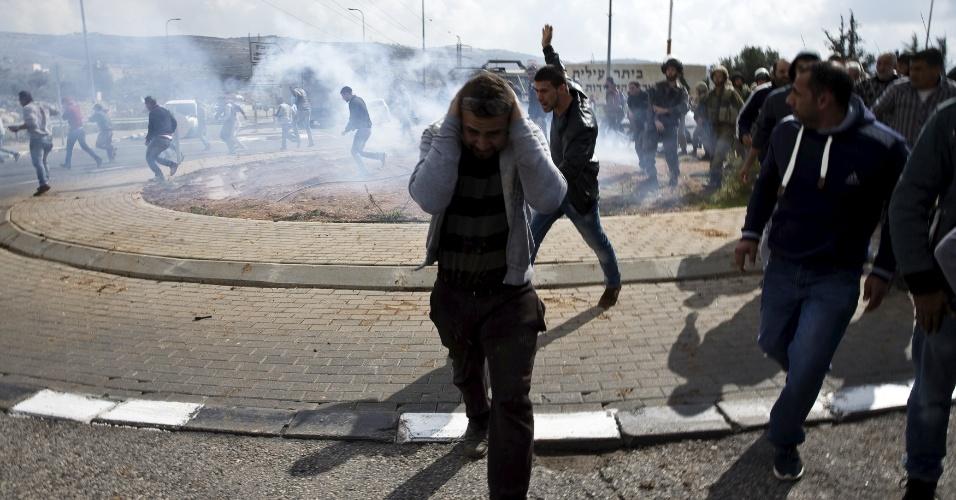 8.nov.2015 - Palestinos correm após tropas israelenses lançarem granadas contra multidão próximo ao local onde houve um esfaqueamento no assentamento judaico de Beitar Illit, na Cisjordânia. Uma mulher foi esfaqueada por um segurança na entrada do local. Hoje, seis israelenses também ficaram feridos em ataques na Cisjordânia cometidos por palestinos, um dos quais foi morto pelas forças de segurança, um novo episódio da onda de violência nos territórios ocupados que começou no início de outubro