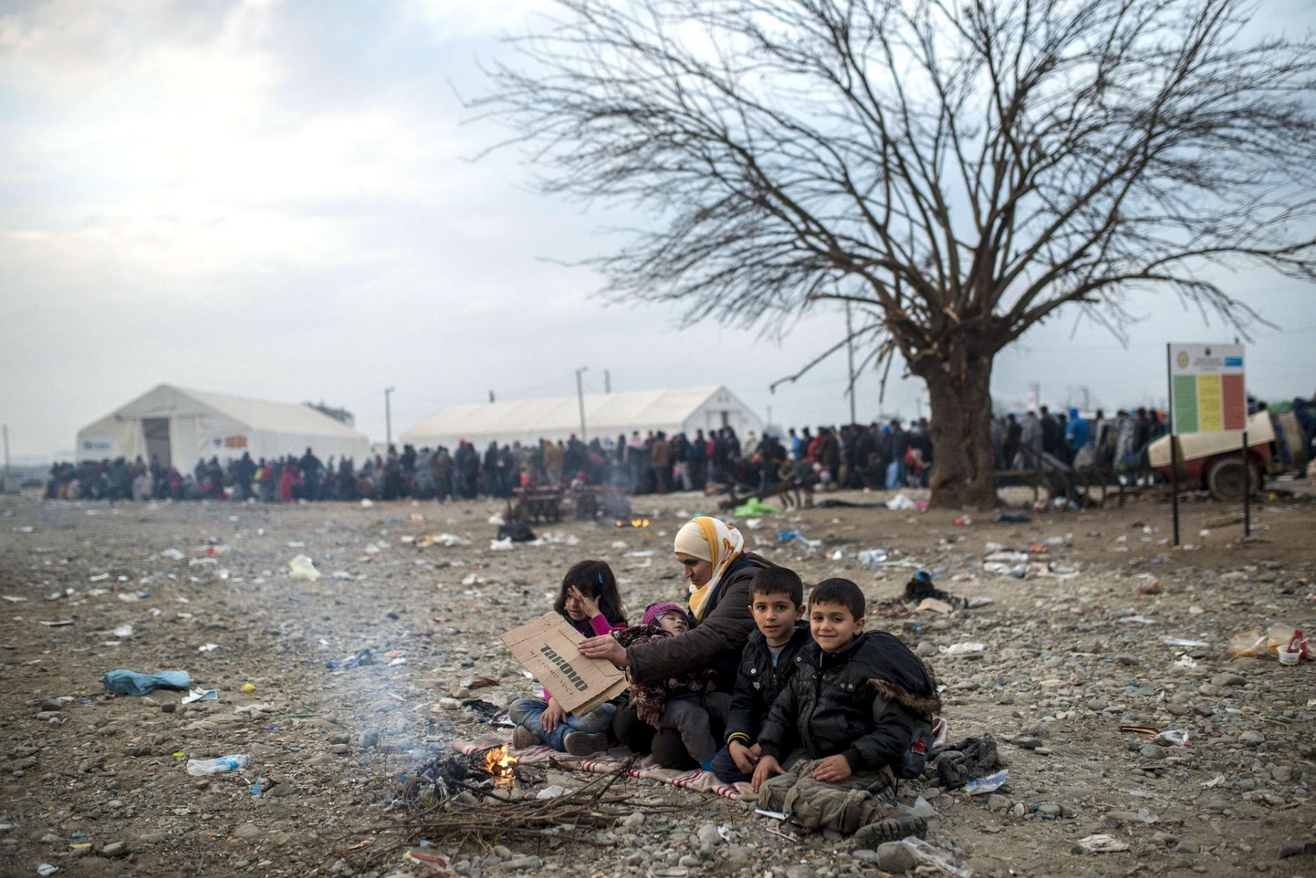 22.nov.2015 - Refugiada e seus filhos tentam se aquecer ao redor de uma fogueira enquanto esperam receber registro de entrada na Europa em região próxima à Gevgelija, entre Sérvia e Macedônia. Uma enorme fila se forma no posto de atendimento que foi erguido no local