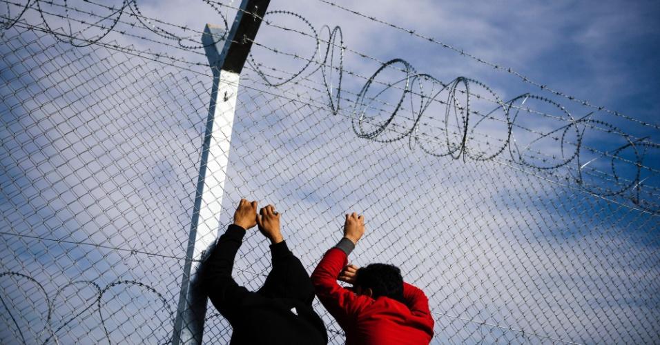 """6.mar.2016 - Dois homens se apoiam em grade com arame farpado na fronteira entre a Grécia e a Macedônia. Neste domingo, o primeiro-ministro Alexis Tsipras acusou a Áustria e países dos Balcãs de """"arruinar a Europa"""" ao diminuir o fluxo de migrantes e refugiados a caminho do norte, saindo da Grécia, onde cerca de 30 mil estão parados, esperando que a Macedônia reabra a sua fronteira para que eles possam ir para a Alemanha"""