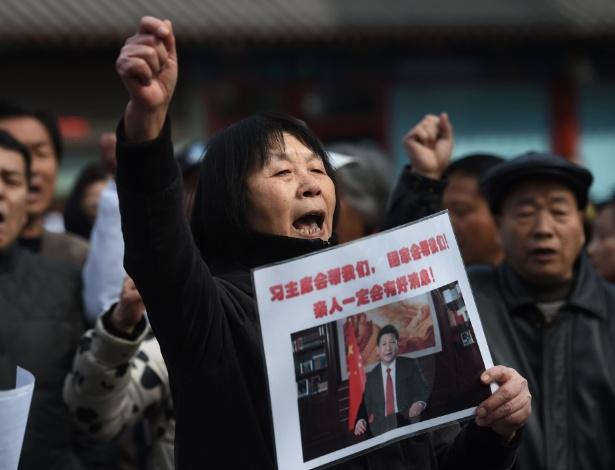 """8.mar.2016 - Dai Shuqin, parente de passageiros desaparecidos no voo MH370, segura cartaz com os dizeres """"O presidente Xi nos ajudará. A nação nos ajudará. Notícias boas sobre nossa família virão"""", em protesto que marca os dois anos do desaparecimento do aeronave da Malaysia Airlines, em Pequim (China)"""