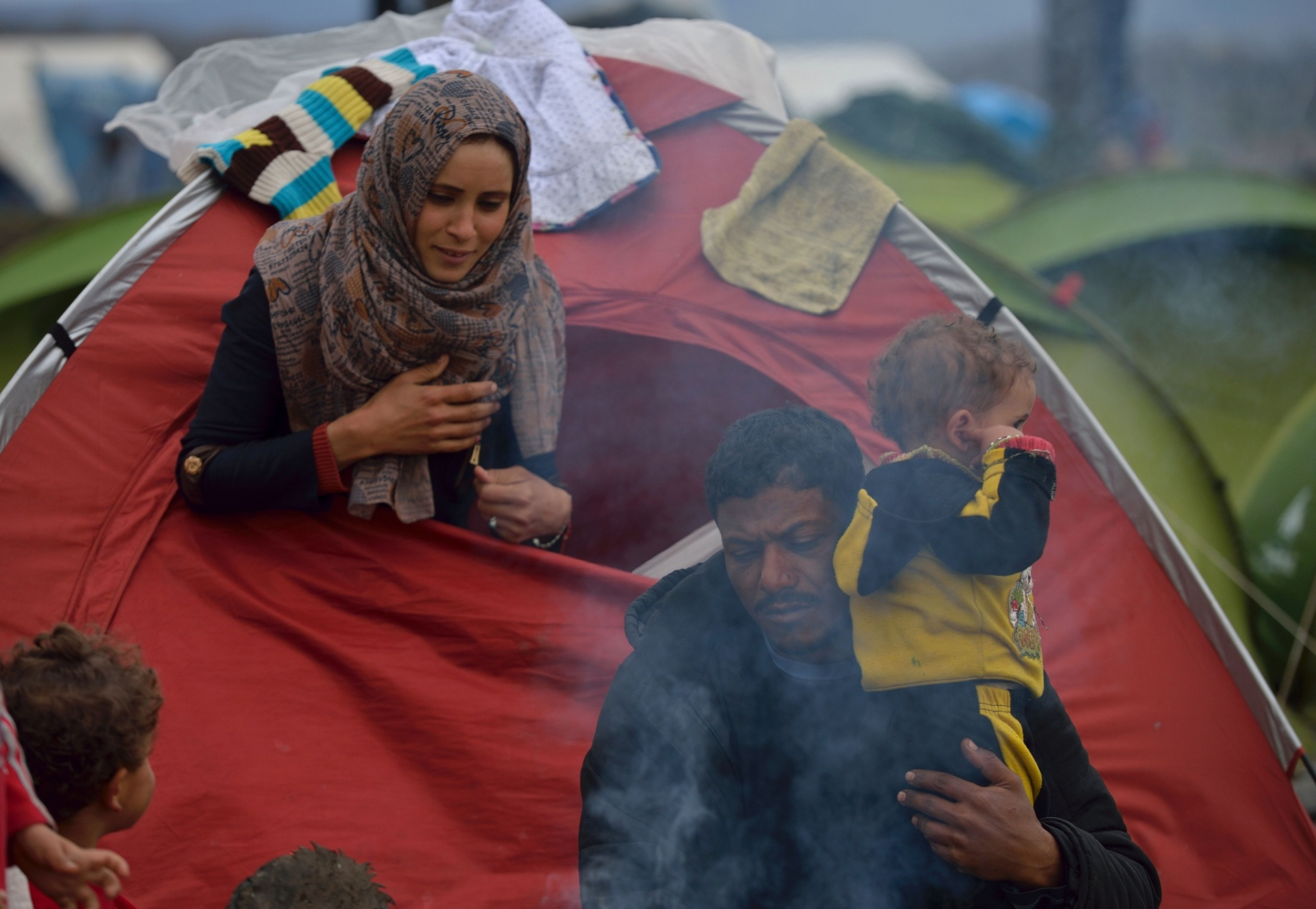 12.mar.2016 - Família começa o dia em acampamento improvisado na fronteira greco-macedónia, perto da aldeia grega de Idomeni, onde milhares de refugiados estão retidos por causa do fechamento das fronteiras nos Balcãs. Mais de 14.000 refugiados, principalmente sírios e iraquianos, incluindo muitas crianças, continuam acampados depois da Macedônia seguir Eslovênia e Sérvia e fechar as fronteiras, impedindo o avanço rumo a países do norte europeu. Trabalhadores de ajuda descrevem as condições no acampamento como