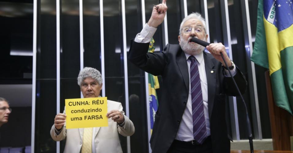 15.Abr.2016 - Parlamentar Ivan Valente (PSOL-SP) discursa durante debate sobre o impeachment da presidente Dilma Rousseff (PT) no plenário da Câmara dos Deputados. Enquanto isso, colega Chico Alencar (PSOL-RJ) segura cartaz em protesto contra o presidente da casa, Eduardo Cunha (PMDB/RJ)