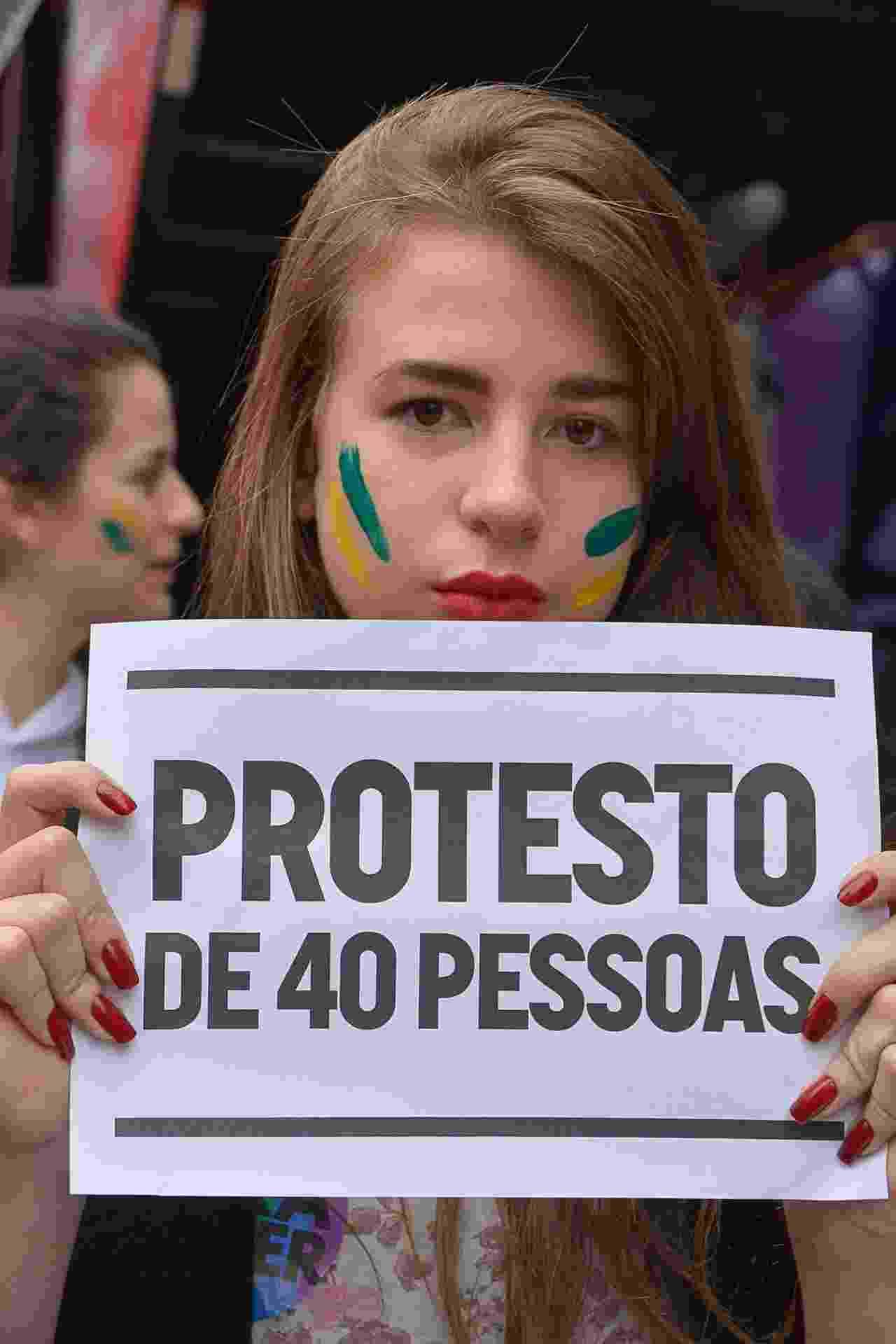 """4.set.2016 - Em protesto na avenida Paulista, em São Paulo, garota com o rosto pintado ironiza a fala do atual presidente Michel Temer (PMDB). Temer havia afirmado que os protestos desta semana eram de """"40 pessoas que quebravam carros"""". A Paulista foi tomada por milhares de manifestantes que pedem a saída do ex-vice de Dilma Rousseff (PT) - Ronaldo Silva/Futura Press/Estadão Conteúdo"""