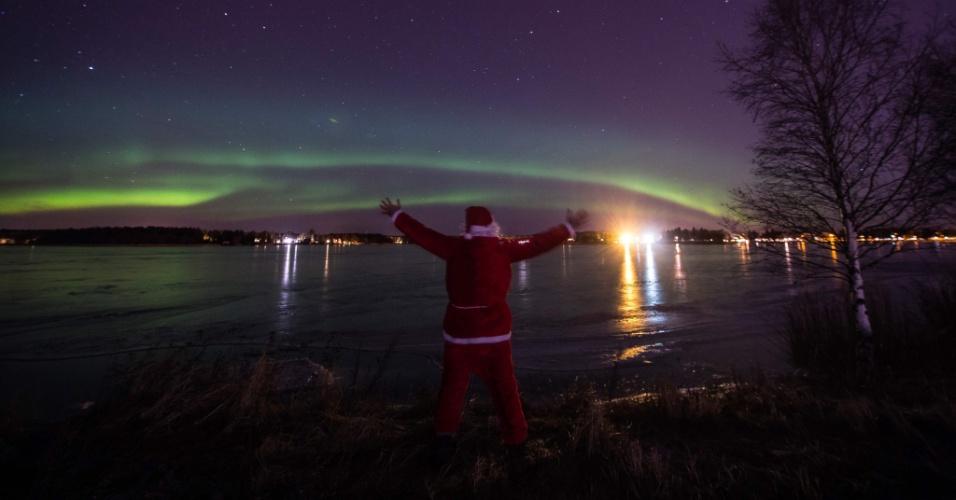 24.dez.2016 - Homem vestido de papai Noel observa luzes da aurora boreal em Vaasa, Finlândia