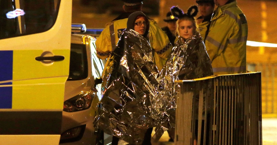 22.mai.2017 - Duas pessoas são abrigadas com cobertores térmicos próximo à Manchester Arena, após atentado depois de show de Ariana Grande