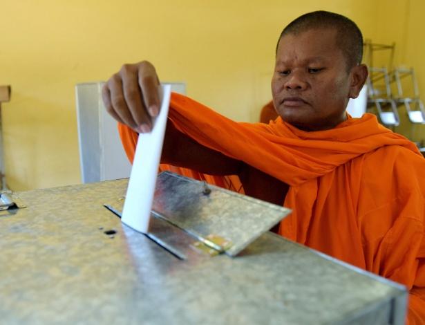 Monge budista coloca sua cédula de voto na caixa, em Phnom Penh, no Camboja