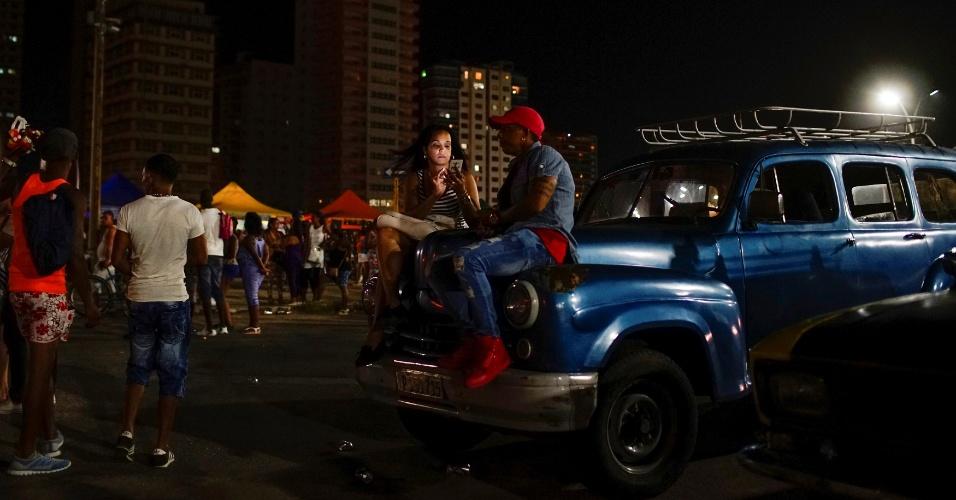 """Mulher usa celular para conectar-se à internet por meio de um """"hotspot"""" de Wi-Fi, em Havana"""