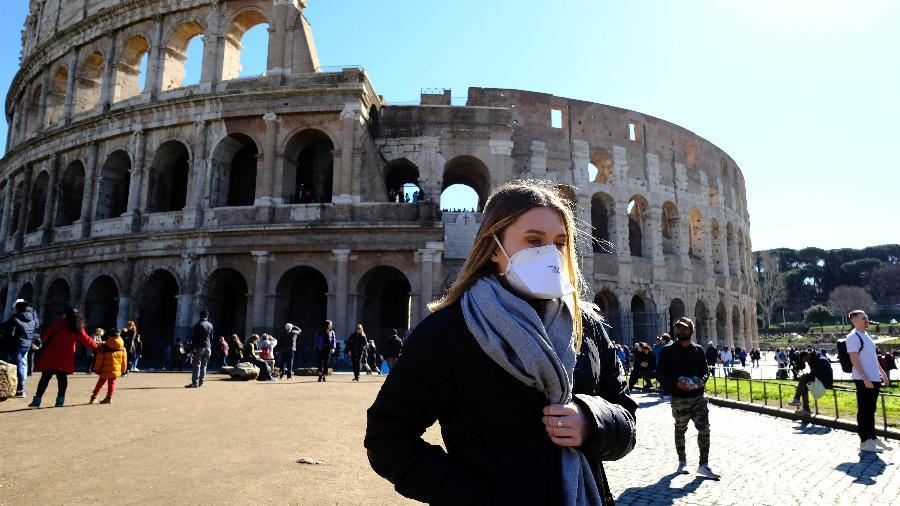 Preocupada com coronavírus, turista usa máscara de proteção perto do Coliseu, em Roma, uma das principais atrações turísticas da Itália - Andreas Solaro/AFP