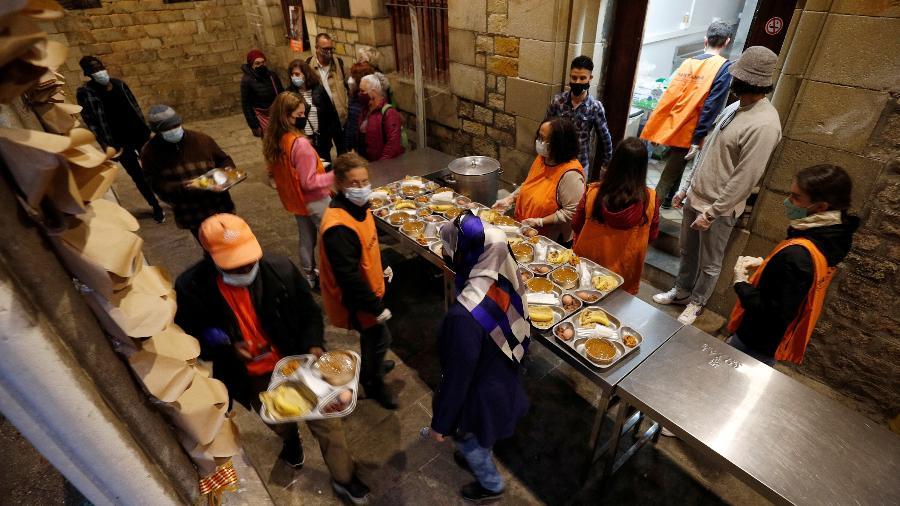 Fila para receber a comida gratuita, para o Iftar, nos corredores da igreja - REUTERS/Albert Gea