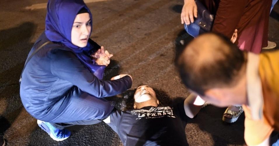 15.jul.2016 - Homem recebe ajuda após se machucar em correria durante tiroteio na ponte do Bósforo, em Istambul, na Turquia. O primeiro-ministro da Turquia, Binali Yildirim, afirmou em rede nacional que o país passa neste momento por uma tentativa de golpe militar. Segundo relatos de testemunhas, as pontes sobre o Estreito de Bósforo, em Istambul, foram fechadas