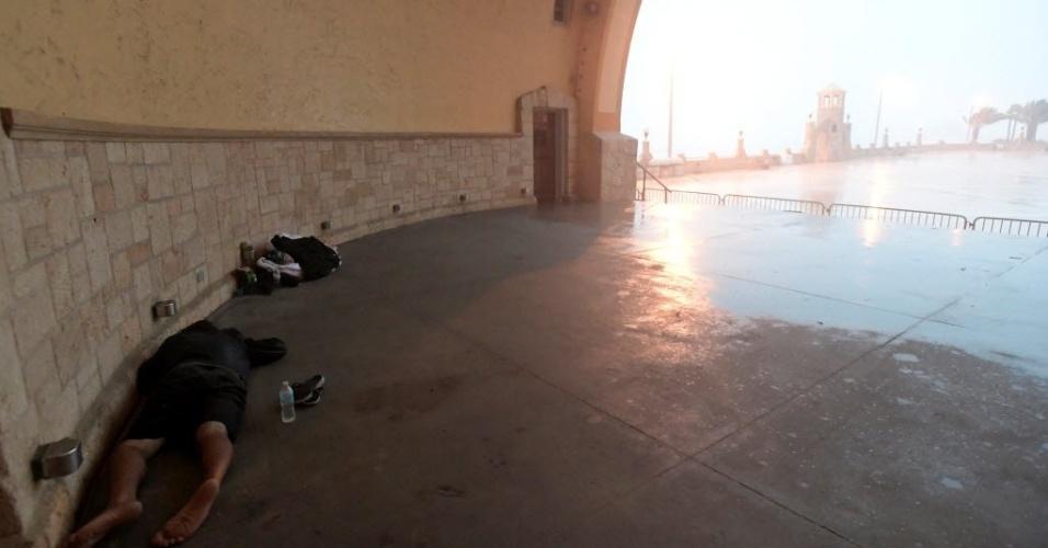 7.out.2016 - Duas pessoas se protegem dos ventos e forte chuva trazida pelo furacão Matthew em Daytona Beach, na Flórida. Os ventos máximos do furacão se aproximaram de 195 km/h, o que fez com que ele caísse para a categoria 3, em escala que vai de 1 a 5
