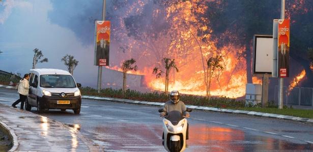 24.nov.2016 - Israelenses passam por incêndio na cidade de Haifa, no norte de Israel