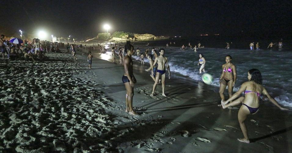 27.dez.2016 - À noite, com a praia menos lotada, os frequentadores têm mais espaço para praticar esportes. Na foto, grupo joga bola a poucos metros do mar
