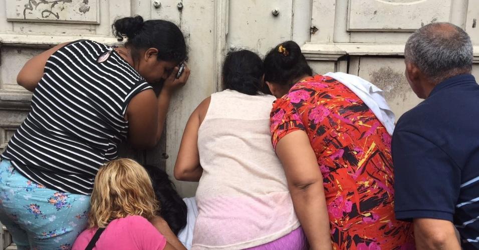 8.jan.2017 - Familiares de detentos espiam pelo buraco da fechadura de portão da Cadeia Pública Raimundo Vidal Pessoa, no centro de Manaus