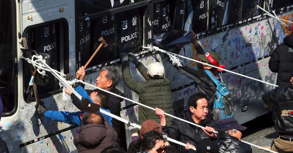 10.mar.2017 - Manifestantes pró-Park quebram e tentam derrubar ônibus da polícia sul-coreana durante protesto contra a aprovação do impeachment da presidente