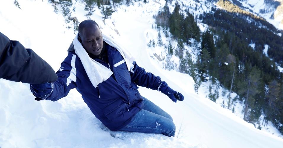 Abdullhai, 38, é ajudado por um amigo para caminhar na neve dos Alpes