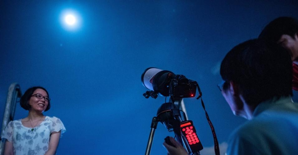 27.jul.18 - Pessoas tiram fotos em frente à lua em Hong Kong