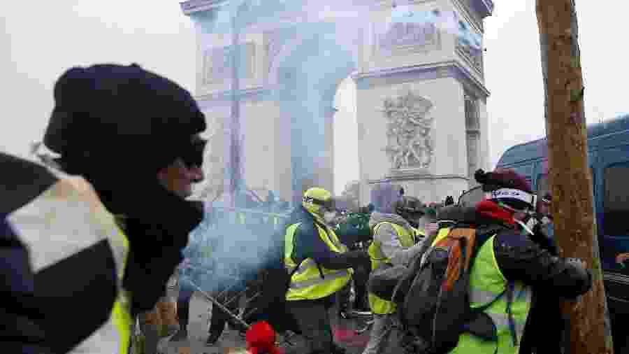 """Manifestantes enfrentam a polícia em frente ao Arco do Triunfo, em Paris. Os agentes usam gás contra os """"coletes amarelos"""" - Stephane Mahe/Reuters"""