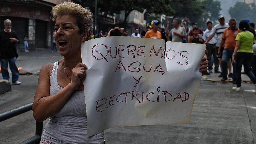 31.03.2019 - Mulher pede água e eletricidade durante manifestação na Venezuela - Federico Parra