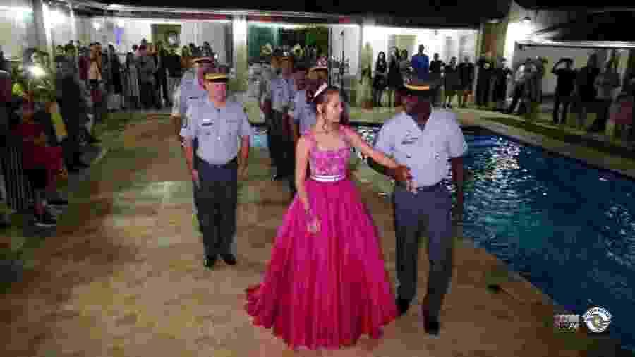A jovem Lívia Caroline entra em sua festa de 15 anos acompanhada de policiais militares - Reprodução/Blog da PMESP