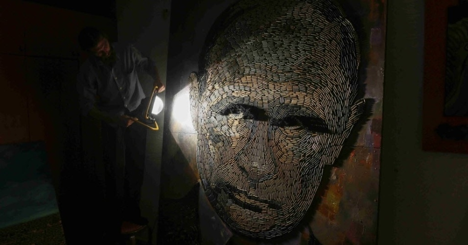 """27.jul.2015 - Retrato do presidente russo, Vladimir Putin, chamado de """"The Face of War"""" (a face da guerra, em tradução livre do inglês), feito com 5.000 cartuchos de balas trazidos da linha de frente do leste da Ucrânia, é apresentado no estúdio da artista Dariya Marchenko, localizado em Kiev. O retrato será apresentado juntamente com um romance que contará histórias de seis pessoas envolvidas no projeto, incluindo gente que ajudou a coletar os cartuchos. Marchenko considera sua arte filosófica, onde cada elemento tem um significado oculto. As obras feitas com cartuchos representam a vida do ser humano encerrada de forma brutal"""