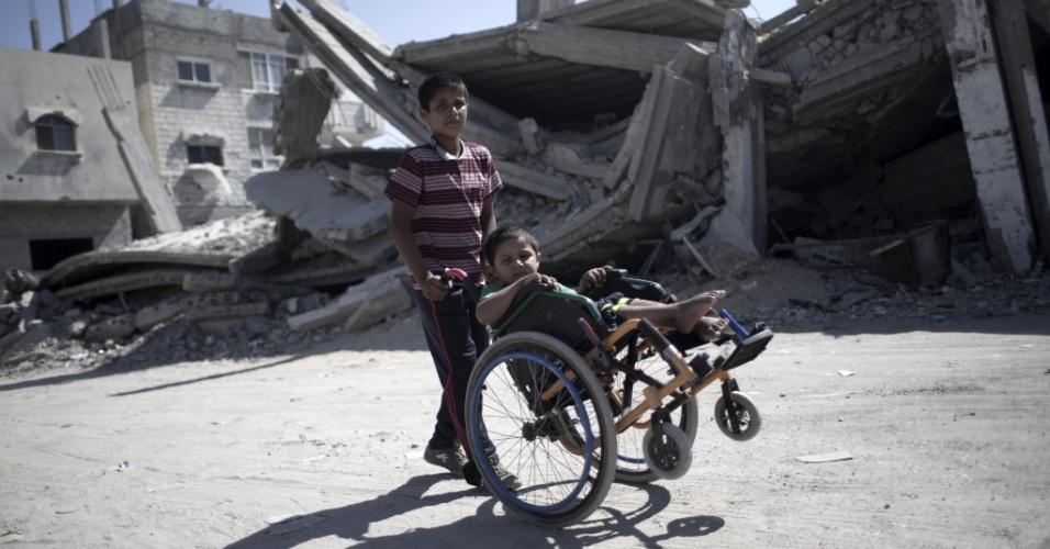 29.jul.2015 - Um garoto palestino empurra a cadeira de rodas do seu irmão, Ayman Mahmoum, que foi ferido durante a guerra de 50 dias entre Israel e militantes do Hamas, no verão de 2014 (no hemisfério Norte). Ayman, 5, foi ferido durante um ataque israelense que ficou conhecido como