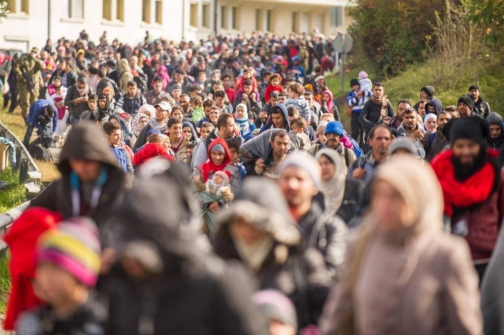 25.out.2015 - Migrantes e refugiados caminham para cruzar a fronteira da Eslovênia para a Áustria neste domingo (25). A Eslovênia pediu à União Europeia forças policiais para ajudar a regular o fluxo de imigrantes