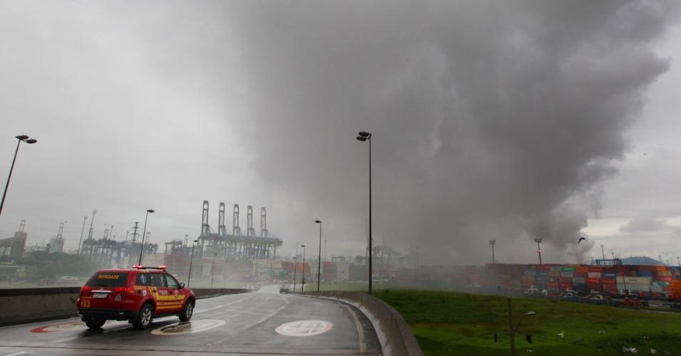 15.jan.2016 - Uma densa fumaça continua sendo expelida um dia depois do incêndio no pátio de cargas do terminal alfandegário da Localfrio, na margem esquerda do Porto de Santos, no Guarujá (SP). Um vazamento de gás seguido de incêndio atingiu o local e espalhou uma nuvem de produtos químicos sobre o litoral sul de São Paulo. O distrito de Vicente de Carvalho ficou isolado pela fumaça, que chegou até a cidade de Santos e provocou evacuação de casas e do cais