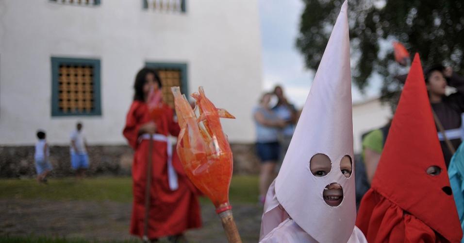 23.mar.2016 - Criança carrega tocha de papel no Fogaréuzinho, em Goiás, versão mirim da tradicional Procissão do Fogaréu