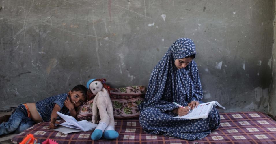 19.abr.2016 - A estudante palestina Huwaida Al-Zaree, de 17 anos, tenta resolver exercícios de um livro didático no sul da Faixa de Gaza