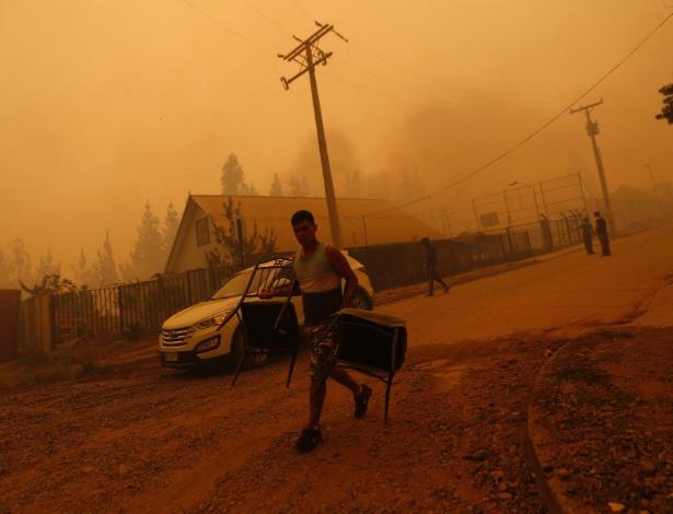 26.jan.2017 - Homem carrega cadeiras em San Ramon após incêndio florestal devastar a vizinha Santa Olga, no Chile - Pablo Vera Lisperguer/AFP