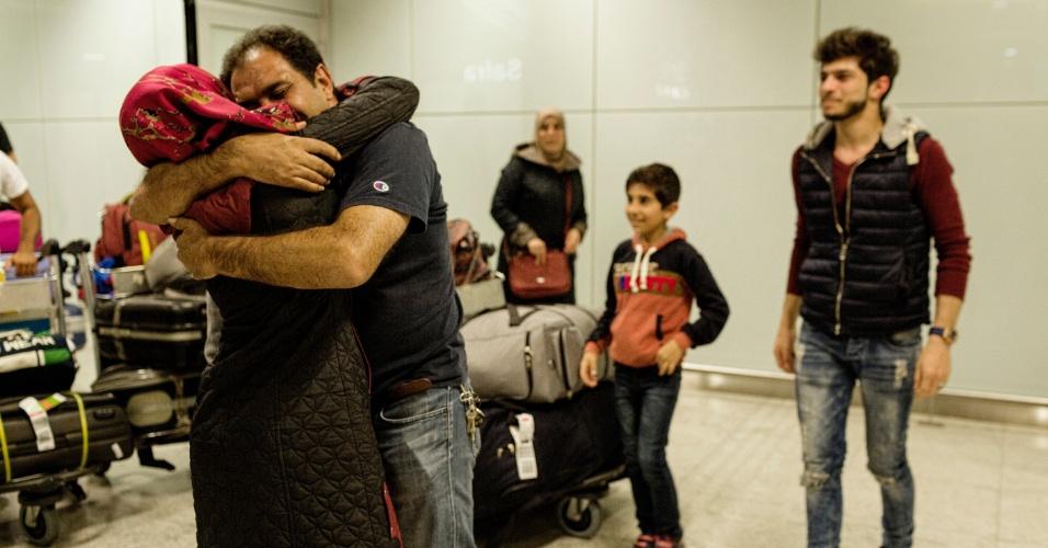13.mar.2017 - O refugiado sírio Adnan Alkhaled abraça a mulher, Bassema, na chegada de sua família ao país no aeroporto de Cumbica