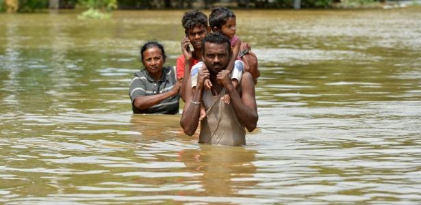 Moradores de Kaduwela, no Sri Lanka, caminham em meio a inundação