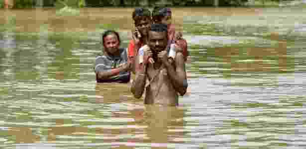 Moradores de Kaduwela, no Sri Lanka, caminham em meio a inundação  - Ishara S. Kodikara/AFP
